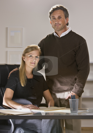 Man and Woman Working in Office stock photo, A man and woman are working together in an office.  They are smiling slightly at the camera.  Vertically framed shot. by Jonathan Ross