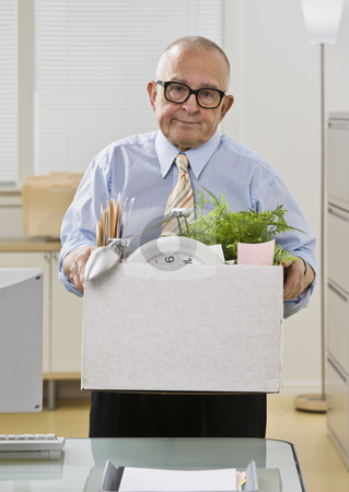 Man Packing up Belongings stock photo, An elderly man is in an office and is holding a box of personal belongings. He is looking at the camera.  Vertically framed shot.. by Jonathan Ross