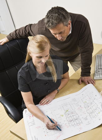 Two architects and the drawing stock photo, Two architects, male standing over female, looking at the drawing on the desk. Vertical by Jonathan Ross