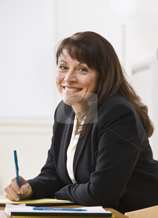 Woman Smiling at Camera stock photo, A businesswoman is seated at a desk and is smiling at the camera.  Vertically framed shot. by Jonathan Ross