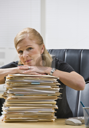 Woman in Office with Paperwork stock photo, A businesswoman is seated at a desk in an office with a stack of paperwork.  She is looking at the camera.  Vertically framed shot. by Jonathan Ross