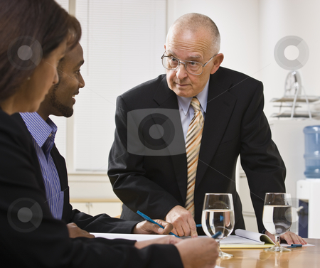 Business team meeting stock photo, Senior male, african American male and white female meeting at desk. Senior male speaking, other listening. Horizontal by Jonathan Ross