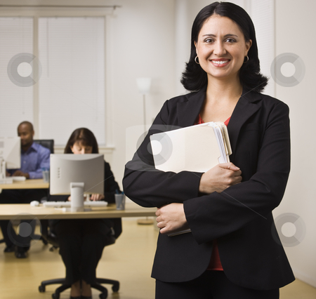 Smiling Career Woman stock photo, An attractive brunette is holding file folders and is smiling at the camera.  She is dressed in business attire and appears to be at her place of employment.  There are people working on computers at the desks behind her.  Square composition. by Jonathan Ross