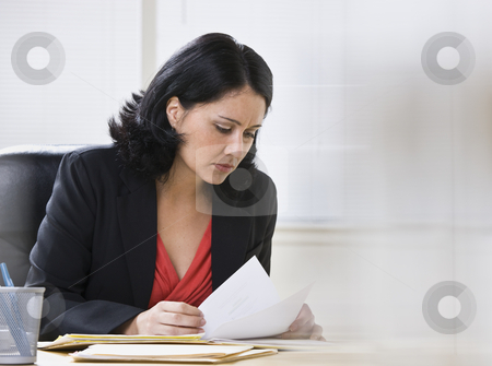 Woman Working on Paperwork stock photo, A young, attractive woman is looking over some paperwork on a desk.  She is looking away from the camera.  Horizontally framed shot. by Jonathan Ross