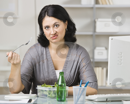 Woman Eating a Tasteless Lunch stock photo, A young woman is eating lunch in her office.  She is looking at the camera.  Horizontally framed shot. by Jonathan Ross