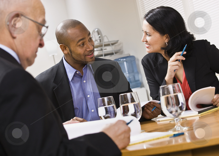 Three attractive business people with water. stock photo, Three attractive business people sitting at a table with water and paperwork. Horizontal by Jonathan Ross