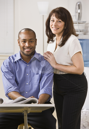 Man and Woman in Office stock photo, A young man is seated in an office and an older woman is standing next to him with her arms on his shoulder.  They are smiling at the camera.  Vertically framed shot. by Jonathan Ross