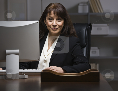 Attractive businesswoman at desk. stock photo, Attractive businesswoman sitting at desk in suit, behind monitor. Looking at camera. Horizontal by Jonathan Ross