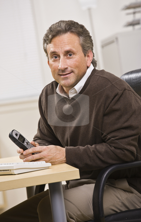 Man Holding Telephone stock photo, A man is seated in an office holding a telephone.  He is smiling at the camera.  Vertically framed shot. by Jonathan Ross