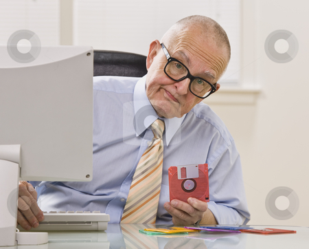 Man with Floppy Disc stock photo, An elderly businessman is seated in an office holding a floppy disk.  He is looking at the camera.  Horizontally framed shot. by Jonathan Ross