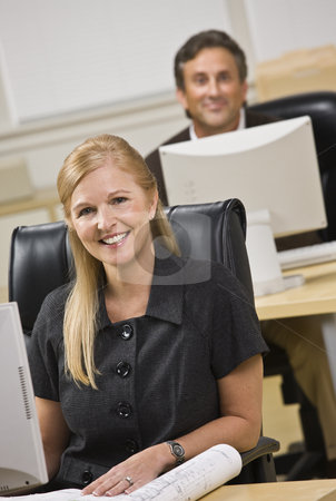Attractive business people sitting at desks. stock photo, Attractive business people sitting at desks. Woman in front, man behind. Smiling at the camera. Vertical by Jonathan Ross