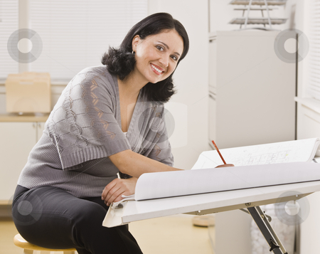 Attractive Woman Writing stock photo, An attractive hispanic woman writing at a desk.  She is smiling at the camera.  Square Composition. by Jonathan Ross