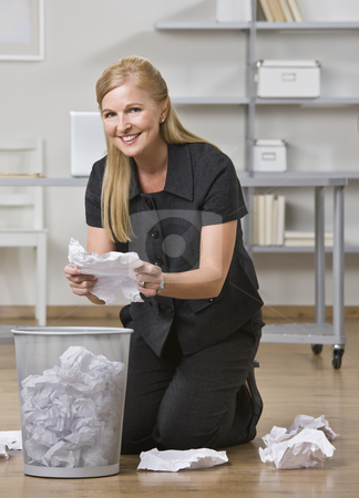 Woman Picking up Trash stock photo, A businesswoman is kneeling at a trash can in an office and is putting all of the paper off the floor into it.  She is smiling at the camera.  Vertically framed shot. by Jonathan Ross