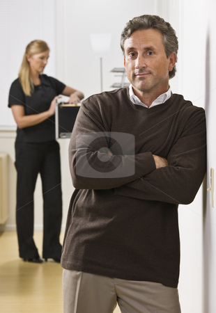 Man and Woman in Office stock photo, A businessman and woman are standing in an office.  The woman is looking in a filing cabinet and the man is looking at the camera.  Vertically framed shot. by Jonathan Ross