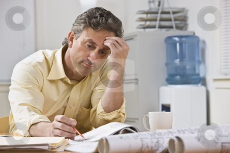 Man Working on Blueprints stock photo, A businessman is working on blueprints in his office.  He is looking away from the camera.  Horizontally framed shot. by Jonathan Ross