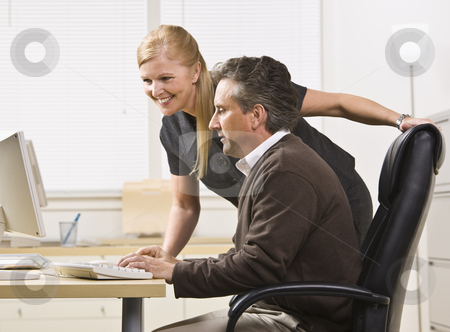 Attractive male and female working on computer. stock photo, Attractive male and female working on computer. Female standing over male sitting at desk. Looking at computer. Horizontal by Jonathan Ross