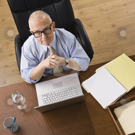 Senior man with laptop. stock photo, Senior man with glasses with laptop, looking at the camera. Square. by Jonathan Ross