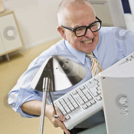 Man Angry at Computer stock photo, An elderly businessman is working on a computer at an office, and appears to be angry at it.  Square framed shot. by Jonathan Ross