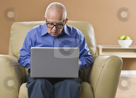 Man on Laptop stock photo, An elderly man is working on a laptop and looking away from the camera.  Horizontally framed shot. by Jonathan Ross