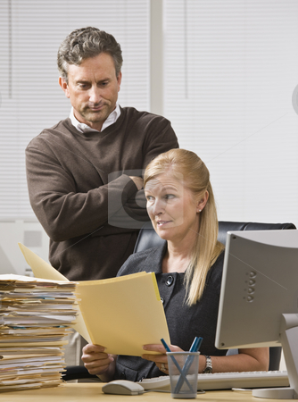 Man Looking over Woman's Shoulder stock photo, A businessman is standing in an office behind the receptionist, and is looking over her shoulder to the file in her hands.  She is looking away.  Vertically framed shot. by Jonathan Ross