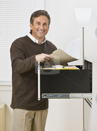 Man Looking Through Files stock photo, A businessman is standing in front of a filing cabinet and is smiling at the camera.  Vertically framed shot. by Jonathan Ross
