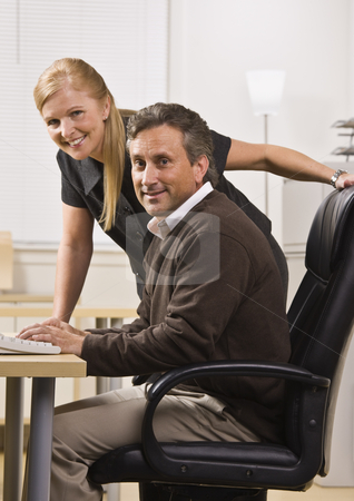 Man and Woman in Office stock photo, A businessman and woman are working together in an office.  They are smiling at the camera.  Vertically framed shot. by Jonathan Ross