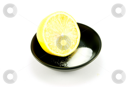Half a Lemon and Salt stock photo, Half a juicy yellow lemon in a small black dish with salt on a white background by Keith Wilson