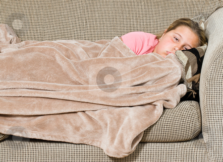 Tired Kid stock photo, A young girl is covered with a blanket on the sofa and about to take a nap by Richard Nelson