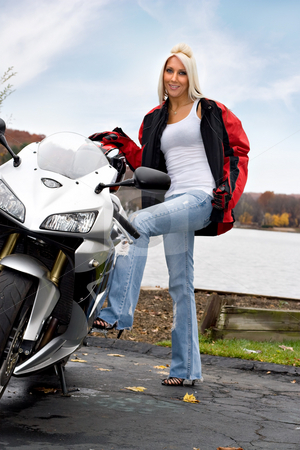 Blonde Biker Girl stock photo, A pretty blonde posing with her motorcycle and riding gear. by Todd Arena