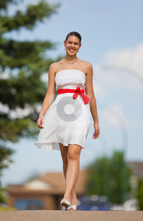 White dress stock photo, Beautiful young woman walking in a city park by Steve Mcsweeny