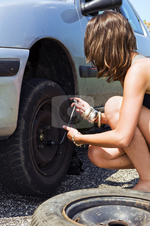 Wheel nuts stock photo, Sexy dressed woman tightening the wheel nuts after changing a flat tire for a spare by Corepics VOF