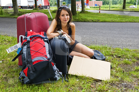 Traveler stock photo, Young woman, resting on her bags, resting at a highway parking lot on her journey by Corepics VOF