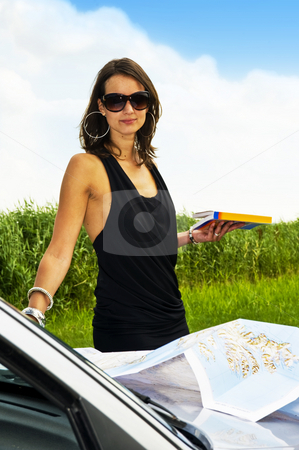 Traveling stock photo, Young classy woman, holding a guide book with a road map on the hood of her car, smiling at the camera by Corepics VOF