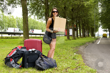 Hitch hiker stock photo, Young, smiling, woman, with a lot of luggage, trying to hitch a ride on a resting place along a busy highway by Corepics VOF