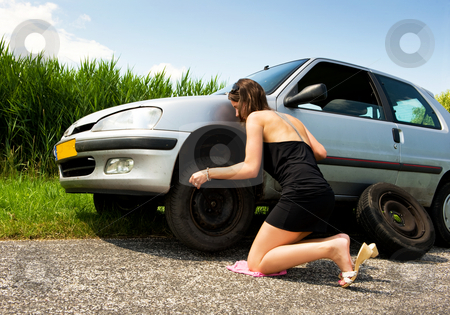 Changing a flat tire stock photo, Young woman, kneeling to tighten the bolts on a spare tire by Corepics VOF