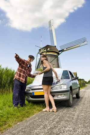 Asking directions stock photo, Young woman, lost on a rural road, asking a local farmer for directions by Corepics VOF