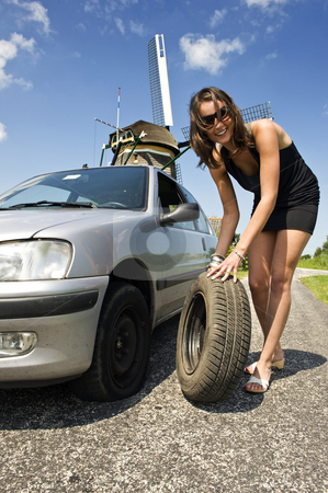 Beautiful Woman Fixing Flat Tire stock photo, Young, confident woman, changing a flat tire on her car on a rural road with a wind mill in the backgrounc by Corepics VOF