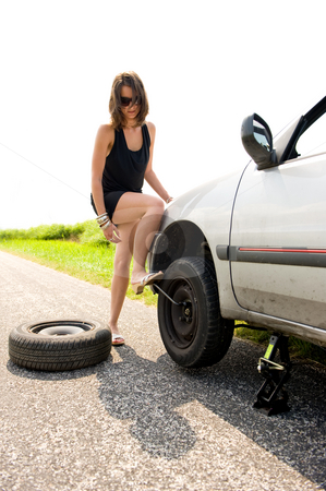 Flat tire stock photo, Sexy brunette aggressively kicking the wrench to tighten the nuts of a flat tire she just replaced by Corepics VOF