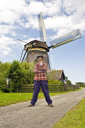 Miller stock photo, Sturdy miller in front of a classic Dutch Windmill by Corepics VOF