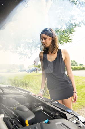 Blown engine stock photo, Young woman looking beaten at the smoke coming from her car's engine by Corepics VOF