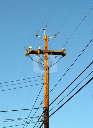 Wooden Telephone pole power pole against blue sky stock photo, Wood telephone pole with power lines coming in many directions by Jeff Cleveland