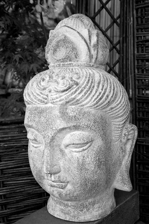 Buda Head stock photo, Black and white buda head statue situated in a garden by Keith Wilson