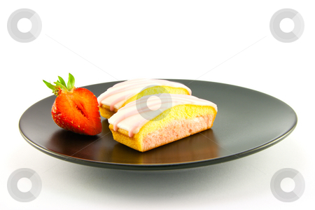 Two Strawberry Slices stock photo, Two pink strawberry sliced cakes with icing on the top with a half strawberry on a black plate on a white background by Keith Wilson