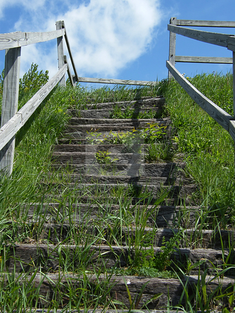 Outdoor Stone Staircase stock photo, Outdoor Stone Staircase. Stone steps and wooden hand rails with grass growing. This staircase (located in Northwest Ohio) leads to the top of a hill . It is a look-out area, to view the land below.  Funny thing is, this look-out area consits of a few average looking homes, a parking lot, and a warehouse. I am inclined to believe this look-out is very old, and was used when the view was once natural and scenic. by Dazz Lee Photography