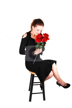 Lady with red roses. stock photo, Young pretty woman, sitting on a bar chair and smelling the red roses in her hand, in an black dress for white background. by Horst Petzold