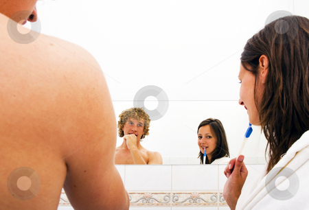 Brushing Teeth stock photo, A couple brushing teeth together in a bathroom looking into the mirror. The man is looking at his girlfriend, the woman is looking at the camera by Corepics VOF