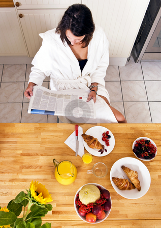 Sunday morning stock photo, Young woman enjoying her lushious Sunday morning breakfast, reading a paper by Corepics VOF