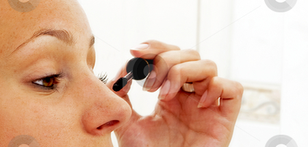Mascara stock photo, A young woman putting on her make-up by Corepics VOF