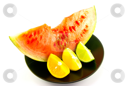 Watermelon with Wedge of Lemon, Lime and Orange stock photo, Slice of red juicy watermelon with a wedge of lemon, lime and orange on a black plate with a white background by Keith Wilson