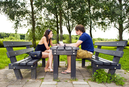 Couple at picnic table stock photo, Young couple at a picnic table, talking and making travel plans by Corepics VOF